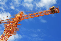Crane and blue sky on building site. Crane and workers at construction site against blue sky Stock Photography