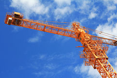 Crane and blue sky on building site. Crane and workers at construction site against blue sky Stock Images