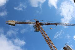 Crane in blue Sky. Photo of a yellow crane in a blue sky on a construction site in brittany france Royalty Free Stock Photography