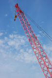 Crane Boom. The red boom arm of a construction crane set against a blue sky with thin clouds stock photo