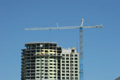 Crane and building. Crane atop steel and concrete construction tower Stock Photography