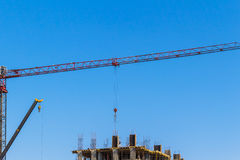 Crane and building construction on blue sky background Stock Images