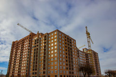 Crane and building construction site against blue sky Stock Photography