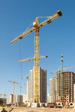Crane and building construction site against blue sky Royalty Free Stock Photos