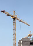 Crane and building construction site against blue sky. Stock Images