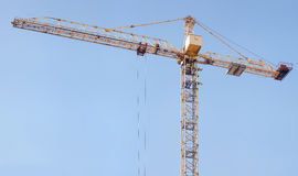 Crane and building construction site against blue sky. Royalty Free Stock Photo