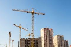 Crane and building construction site against blue sky. Stock Photos