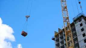 Crane and building construction site against blue sky. heavy load hanging on the hook of a crane on the construction of Royalty Free Stock Photos