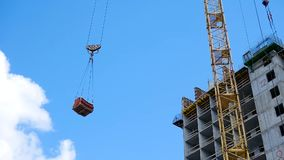 Crane and building construction site against blue sky. heavy load hanging on the hook of a crane on the construction of