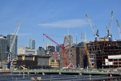 Crane and building construction site. APRIL 2016-NEW YORK CITY : Cranes and building construction site against blue sky in New York City, NY in April 2016 Royalty Free Stock Images