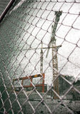Crane at building site. Seen through cgain link fence and protective net royalty free stock photo