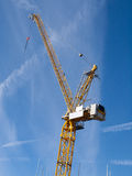 Crane on building site. Detail of a yellow crane isolated against blue sky Stock Photography