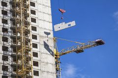 Crane and building under construction against blue sky. Stock Images