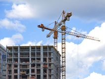 Crane and building under construction against blue sky. Royalty Free Stock Image
