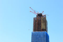 Crane and building under construction site. On sky background Stock Photos