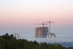 Crane with buildings in the morning. Fog Royalty Free Stock Photography