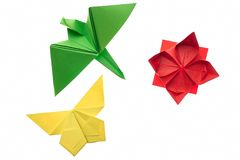 Crane, butterfly and lotus origami. On white. Red, green and yellow paper. Hand crafting project idea for kids royalty free stock photo