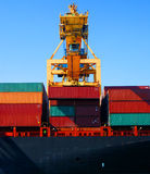 Crane & cargo containers. Rows of shipping containers, with a large crane overhead, lifting more containers into place stock image