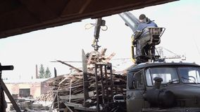 Crane claw loader unloads timber scraps from heavy truck at sawmill facility. Cold cloudy winter day stock video footage