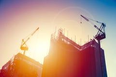Crane con el edificio inferior de la construcción con el cielo de la puesta del sol Fotografía de archivo