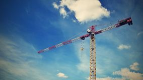Crane on construction with blue sky clouds and sun in the background. Stock Photos