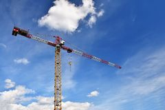 Crane on construction with blue sky clouds and sun in the background. Stock Photo