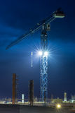 Crane. Construction. Night sky. Tall lifting crane and construction at dark blue sky background. Vertical orientation photo stock photo