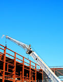 Crane at Construction Site. Crane working on new building construction with blue sky above Royalty Free Stock Images