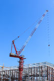 Crane at construction site against blue sky Royalty Free Stock Photos