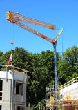 Crane at construction site with blue sky Stock Photos
