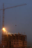 Crane on the construction site, unfinished house, fog, evening twilight, building lighting Stock Photo