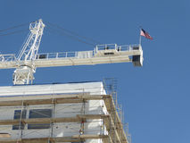 Crane at construction site. White Crane at construction site with american flag Stock Image