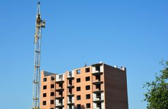 Crane construction with unfinished building and working contract stock photography
