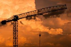 Crane Construction utrustningkontur på solnedgånghimmel som förbluffar färgrik molnbakgrund i aftonen royaltyfri foto