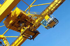 Crane for containers. Bottom view of industrial crane for cargo on blue sky Stock Image