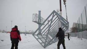 Crane a cubeta durante a instalação com construção durante o quadro de avisos grande da instalação no mau tempo Os trabalhadores  video estoque