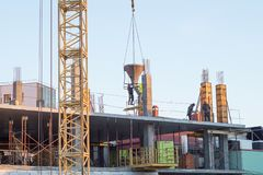 Construction of a multistory building. workers pour concrete into the formwork. stock images
