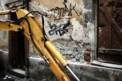 Crane in desolated district. Yellow crane working on renovations of a desolated district inside a city. Half-destroyed walls of buildings are covered by graffiti stock image