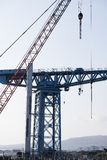 Crane detail on construction building site lifting freight containers stock photos