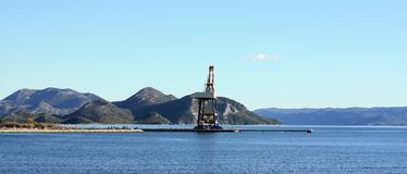 Crane dominating the scene. Harbour near City of Ploce. Ploce,  Ploče . Cargo harbour entrance with single crane. Sea in foreground. Mountains in background Royalty Free Stock Photography