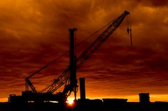 Sunset Construction Site. Crane and a drill standing tall at sunset Royalty Free Stock Photo