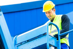 Crane driver driving hydraulic lifting ramp with control desk Royalty Free Stock Photography