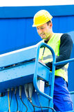 Crane driver driving hydraulic lifting ramp with control desk Stock Image