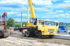 Crane driver works to set precast concrete piles for repair road. Saransk, Russia - July 19: Auto crane Kamaz 55713-1. Crane driver works to set precast concrete royalty free stock photo