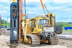 Crane driver works to set precast concrete piles for repair road Stock Photos