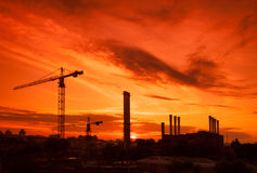 Crane en el emplazamiento de la obra bajo puesta del sol Fotografía de archivo libre de regalías
