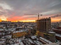 Crane en el emplazamiento de la obra bajo puesta del sol Imagen de archivo libre de regalías