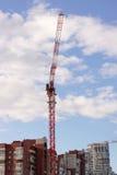 Crane en un fondo de casas y un cielo azul con las nubes imágenes de archivo libres de regalías
