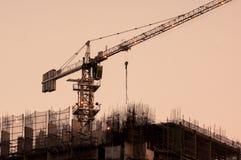 Crane encima de un edificio inferior de la construcción en la oscuridad Fotos de archivo