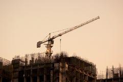 Crane encima de un edificio inferior de la construcción en la oscuridad Fotografía de archivo libre de regalías